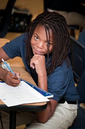 Student Smiling while taking notes